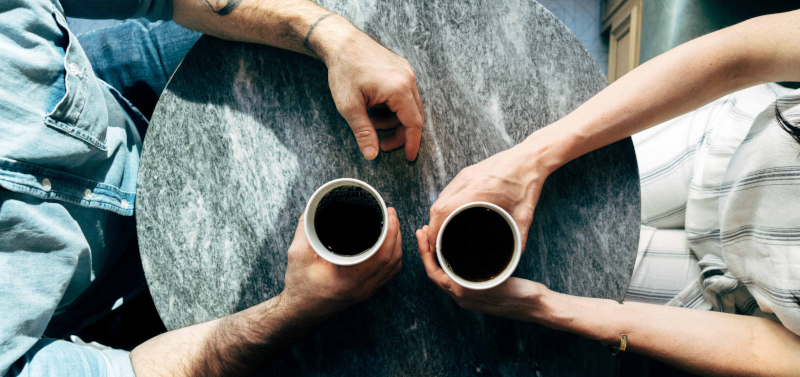aerial view of a cafe table with two people sitting opposite each other holding coffee cups