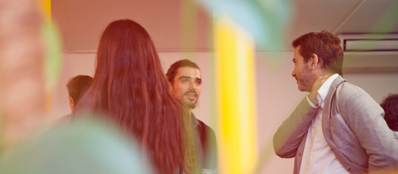 two men talking in a room taken through a coloured light lens